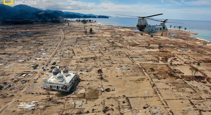 A U.S. Marine helicopter loaded with food flies over Lampuuk in northern Sumatra on January 4, 2005, nine days after a tsunami killed most of the village's 7,000 residents and some 230,000 people on coastlines around the Indian Ocean. Many locals believe divine intervention saved the Rahmatullah mosque. ©John Stanmeyer/National Geographic