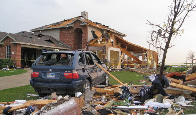 An SUV sits next to a damaged home in Forney.